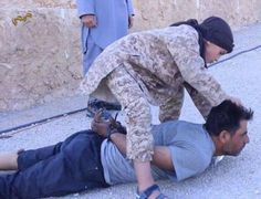 """pp: """"Brutal murder: The regime soldier is seen being forced to lay on his stomach as the young boy approaches him from behind, pulls his head back by the hair, and uses a small knife to behead him"""""""