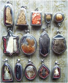 Animal and Plant Reliquary Pendants - Forest Grove Botanica  From the top left: Mandrake, Henbane, Fly Agaric, Acorn, Snail, Turtle, Robin, Raven, Barn Owl, Rat, Crow, Snake, Toad, and a Deer tooth.