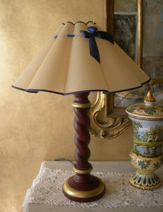 This classic dark red turned wood lamp base on a round base is handcrafted in Italy and it's configured to fit European Uno lampshades. With an ha...