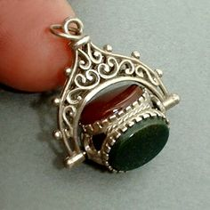 An Enchanting Vintage Sterling Spinner Watch Fob Charm Gemstone Pendant embellished with Double-Sided Intricate Byzantine Filigree Scrolls and tightly set with Genuine Carnelian, Black Onyx, and Bloodstone Gemstones in a Guaranteed Sterling Silver Setting, Original Soldered Close Bail, Weight 2.9 Grams, Perfect Vintage Condition!  Approx. Measurements are 1 in length by 3/4 in width (not including the top jump ring).  This Sterling Fob Charm is so Sweet and Lacey! It is a Spinner where ...