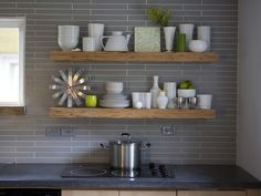 This grey backsplash tile with contrasting white grout could have been laid in the traditional pattern. But an offset pattern, along with a matte finish and extra narrow shape, is thoroughly modern. By displaying white dishware on the open shelves, the ho Floating Shelves Kitchen, Kitchen Shelves, Kitchen Backsplash, Open Shelves, Wood Shelves, Easy Shelves, Plywood Kitchen, Wall Shelving, Kitchen Cabinets