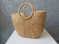 Handwoven seagrass tote, perfect for summer! Tote is made of natural sea grass, with a beige cloth liner. The simple and lightweight design is the ideal size for carrying summer accessories on the go! Each piece will have slight variations to complement the authentic look of the product.  Tote is approximately 15in. wide at the top and 10in. wide at the bottom. The height at the top of the bag is 10in. while the handle extends the total height to 14in., bag is 5in. in diameter.