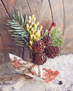 A rustic boutonniere with pinecones and pine