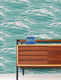 The latest in the Mini Moderns collection. Whitby, their nautical-but-nice wallpaper design is inspired by 1950s linocuts, Whitby captures the majesty and beauty of the open sea.  The print features a pair of brave fishing boats, circled by a flock of hungry seagulls. The bold wave motif creates the effect of the sea morphing into a cloudy sky, forming a dramatic horizontal stripe. The colours of weathered seaside awnings and fisherman's overalls informed the palette.Available in 4 styles...