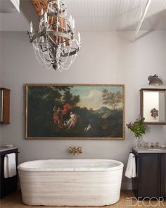 A vintage Italian chandelier hangs above an antique tub.