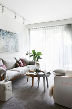 House tour: a light, contemporary apartment in Melbourne: Above a 'Wilfed' sofa by Jardan hangs an artwork by Belinda Fox from Scott Livesey Gallery. On the 'Around' coffee tables by Muuto sit a terrarium from Totokaelo and 'Kaleido' tray by Hay.