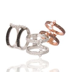 This trio of River rings - set with either black, champagne, or white diamonds, are set in rose or white gold, with a double-band style and trail of diamonds connecting the ends.