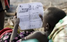 A Burundian refugee child reads a book on the shores of Lake Tanganyika in Kagunga village in Kigoma region in western Tanzania, as they wait for MV Liemba to transport them to Kigoma township, May 18, 2015. REUTERS/Thomas Mukoya