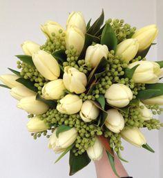 Bridal wedding bouquet of cream tulips, berzillia, and magnolia foliage.