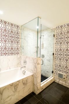 Marble sunken tub and glass shower stall with ornate black and white wallpaper with sort of a Moroccan feel to it! http://cococozy.com