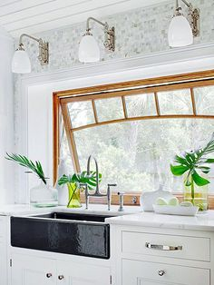 In an otherwise traditional white kitchen, this black cast-iron farmhouse sink commands attention. Accents with shine, such as the chrome cabinet pulls, the trio of lights above, and the bridge-style faucet keep the room bright.