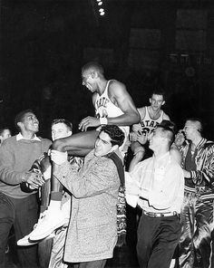 A group carries basketball players on shoulders, 1957 by Michigan State University Archives, via Flickr