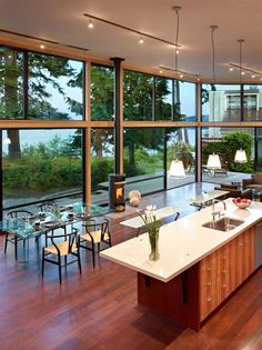 I like how the kitchen is open to the dining area and living room. Glass Walled Waterfront Residence by Finne Architects