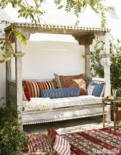 Vintage textiles enliven an Indonesian daybed; seat cushion in Great Outdoors' Fresh Canvas.