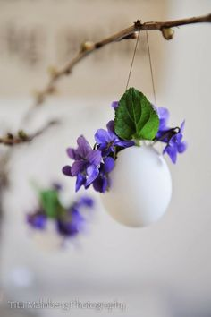 Cute Easter egg decorations made with eggs, flowers and hung like ornaments from tree branches.