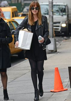 Off duty style: Dakota Johnson looked chic in her black mini dress and leather jacket as she strolled around New York on Friday, x