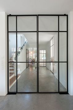 Monumentale Villa Bussum - Beautiful thin black metal frame glass doors. I love the somewhat industrial style with the concrete flooring and white walls. #InteriorDesignContemporary
