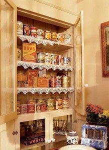 Un antiguo armario de la limpieza se convirtió en un armario despensa puerta de vidrio, con un vaso de edad que se encuentra en la casa.  Los propietarios pegar las etiquetas de enlatado período no utilizados a las latas estándar, a su vez-de-siglo de tamaño de pantalla en el frente.