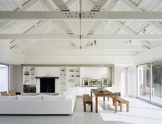 Family room with white sectional sofa, high ceiling with exposed beams, white bookcases a fireplace, picture windows and a long wood table w...