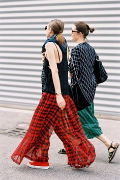 Left: A black tank top is worn with sheer plaid pants, red tennis shoes, a striped sweater, and sunglasses. Right: A printed short sleeve top is worn over a green and black striped midi skirt, sandals, sunglasses and a black bag.