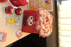 Elmo themed cake pops (elmo face, red with sprinkles and plain red).  Wrap small box in red wrapping paper.  Use a screwdriver to makes holes for the pop sticks and use construction paper for Elmo's face on the box!  Homemade Elmo cake-pop stand!  #Elmo #BirthdayParty #SesameStreet