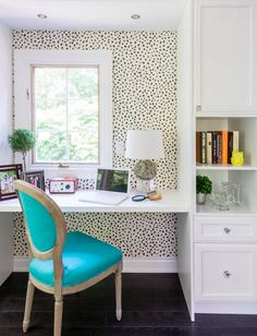 Charming workspace with spotted wallpaper and a bright aqua chair. home office…