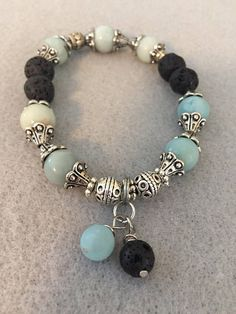 Diffuser Bracelets. Available in blue Amazonite , Red Quartzite, Carved Soapstone , White Turquiose Howlite , Beige Moonstone. Silver Plated Accents with black lava rocks. Black lava rocks can be scented with a favorite essential oil , fragrance oil or perfume. Available in multiple