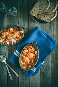 Prawn Saganaki | 250 grams fresh prawns, cleaned deveined and tails left intact, 1/4 cup olive oil, 1 red onion finely diced, 2 cloves garlic, finely minced, 1 long red chili, finely chopped, 1 large bullhorn or banana chilli, finely sliced, 2-3 tbsp ouzo, 200 grams canned tomatoes (or 2 large tomatoes pureed in a blender), 1/4 cup freshly chopped, flat leaf parsley, salt and pepper for seasoning, 100 grams feta cheese.