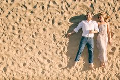beach engagement photos stand near pier to get view from above