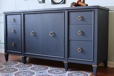 The finish on this mid-century credenza was inspired by the original owner's dashing pilot uniform. To get the perfect navy, Annie Sloan Stockist me & mrs. jones in Memphis, TN mixed Chalk Paint®️️ in Napoleonic Blue and Graphite in equal parts. They dampened the paint and burnished it smooth with 600-grit wet/dry sandpaper. To finish off the look, they also freshened up the original brass hardware.