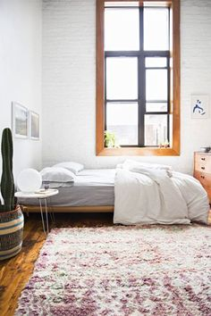 """20 Of The Coolest Rooms In New York City #refinery29 http://www.refinery29.com/cool-rooms-nyc-apartment-pictures#slide-12 With a window like this one, sunlight's the star. """"White brick and the simplest low-slung bed help make the most of this bedroom's natural, ethereal light,"""" says designer Jenny J. Norris."""