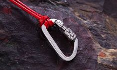 "Sterling Pendant Locking Carabiner. Mountaineering and от ExJe  A carabiner (/kærəˈbiːnər/) or karabiner is a metal loop with a spring-loaded gate[1] used to quickly and reversibly connect components, most notably in safety-critical systems. The word is a shortened form of Karabinerhaken, a German phrase for a ""spring hook""[2] used by a carbine rifleman, or carabinier, to attach items to a belt or bandolier."