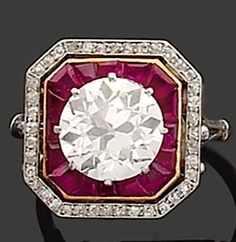 *RING Art Deco platinum and yellow gold, with a diamond weighing approximately 2.40 carats surrounded by calibrated rubies and diamonds. Around 1925 .