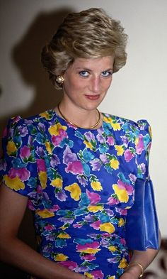 On a visit to Nigeria, Diana pulled out all the stops in a vibrant, multi-coloured floral gown paired with an electric-blue handbag and eyeliner to match. (Photo by Jayne Fincher/Princess Diana Archive/Getty Images) Lady Diana Spencer, Princess Diana Fashion, Princess Diana Pictures, Floral Gown, Floral Dresses, Diane, Princess Of Wales, Real Princess, Up Dos