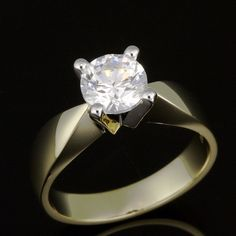 Prong set diamond solitaire with inward tapered raised solid shoulder band. Classic perfection - flowing tapered lines enhance an open prong set solitaire Diamond.