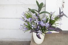 Again, using the purple heart as structure, build out the shape of the arrangement in another simple clay vase. Then add the agapanthus bloo...