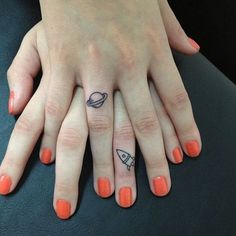 Little finger tattoos of planet saturn and a rocket.