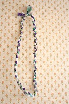 A braided necklace - how simple is that? Could probably use some of those old scarves the kids used to play with.