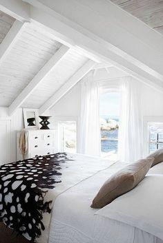 Une chambre avec poutres dans une maison de vacances - Une chambre mansardée est souvent basse sous plafond, comme dans cette maison de vacances au bord de la mer à Cape Town. Evitez de sur-meubler, car les poutres et les lambris en bois du toit, même peints en blancs, sont déjà très présents. Un lit avec un joli couvre-lit décoratif, une commode et des voilages aériens à la fenêtre : voilà tout ce dont vous avez besoin pour la déco de votre chambre.