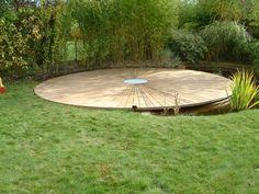 Terrasses en bois arrondies dans un jardin au milieu d'un étang