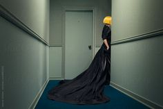model wearing a wig in a hallway with green walls by Ulaş and Merve for Stocksy United