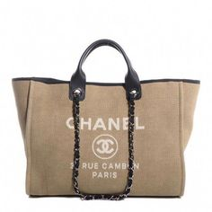 60c96b4c31ff ... an authentic CHANEL Canvas Deauville Large Tote in Beige and Black.  This lovely tote is crafted of fine canvas with a white printed  advertisement logo.