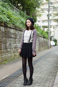 Lavender cardigan, cute top, black skirt, boots, and cute hat.