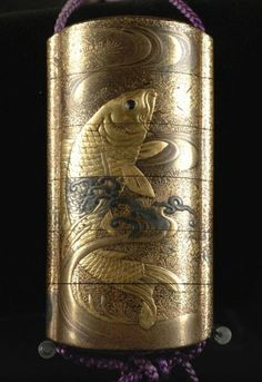 This five box inro depicts an overall scene of two carp among waves. The eyes of the carp are inset glass with black pupils. The interior is red speckled gold. More