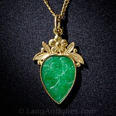 A rich green jadeite drop, hand carved with a charming floral motif, is bezel-set in 22 karat yellow gold and crowned with complimentary golden floral arrangement in this delightful necklace by way of mid-20th century China or Hong Kong