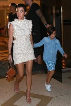 Kourtney Kardashian wearing Chloe Georgia Convertible Leather Belt Bag and Alaia Cutout Glossed-Leather Sandals