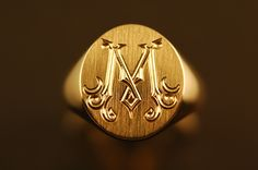 "This 14x18mm Die Struck 14k Signet Ring is engraved with a sculpted victorian style ""M"". By deeply bright cutting and faceting the character's interior to contrast the brush finished surface of the ring, a dramatic contrast of light and energy results. Characters engraved in this manner also make fine wax seals."