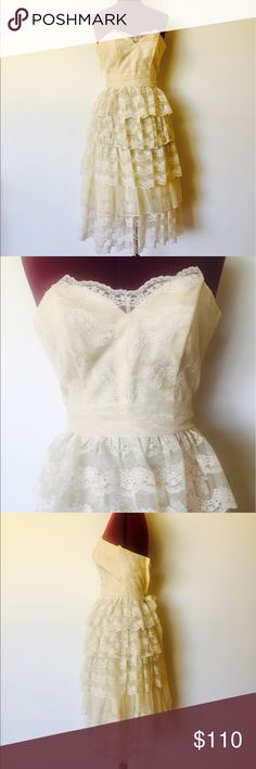 """Vintage 80s Lace Ruffles Wedding Dress XS 80s strapless dress in off white lace and an antique taffeta underlay. The top has plastic boning at the bust and sides with two styles of lace and scalloped lace at the top. The skirt has five tiers of lace ruffles. It has a wide lace belt and zips up the back with a nylon zipper. Would make a lovely wedding dress.     Material: Nylon, acetate Maker: Electra Size:3/4  Bust- 31"""", extra space for up to a small B cup Waist- 23"""" Hips- 40"""" Length-  28.5""""…"""