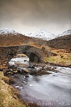 A dramatic Scottish winter landscape with a bridge, frozen river and mountains in the background
