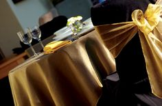 Black chairs with gold tablecloth/sash